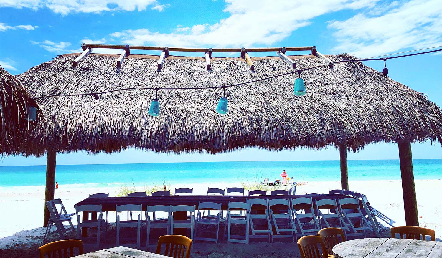 Long table under tiki view of blue gulf waters in background